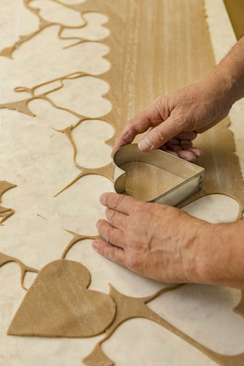 cropped hands are cutting dough with a cutter in the shape of a heart Hand Art And Craft Indoors  Holding One Person Human Hand Human Body Part Gingerbread Heart