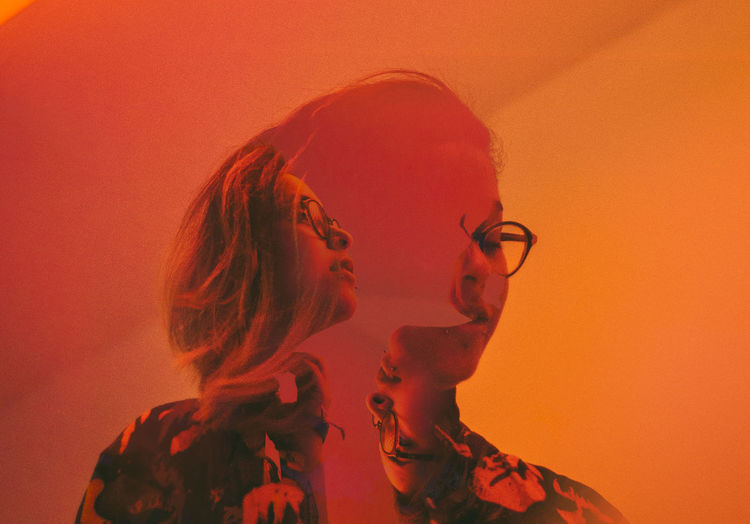 Digital composite image of woman in eyeglasses against orange background