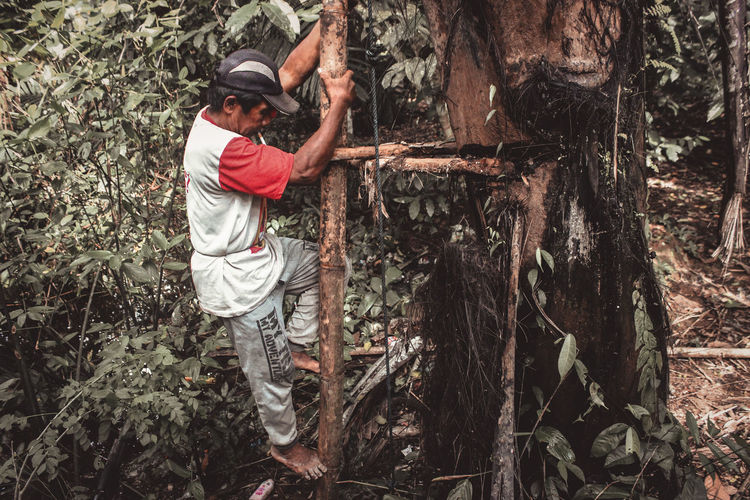 Full length of man holding tree trunk in forest