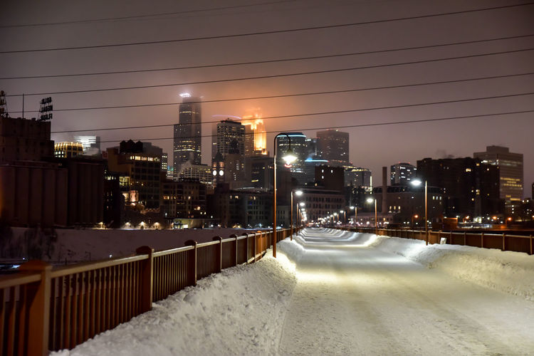 Illuminated snow covered bridge in modern city at night