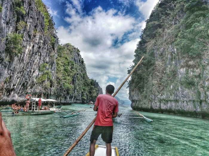Rear View Of Man Standing On Boat In Sea Amidst Rocky Cliffs At El Nido