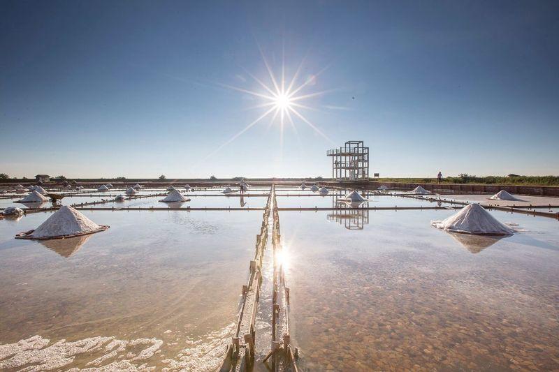 View of salt pans against blue sky