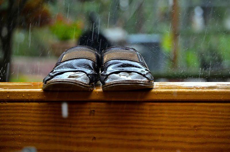 Slipper on wooden table during rainy season