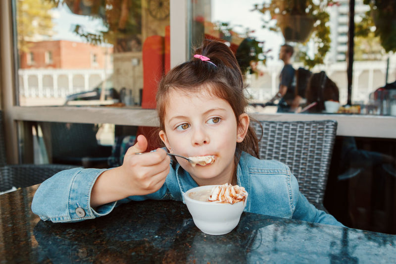 Girl eating food at restaurant