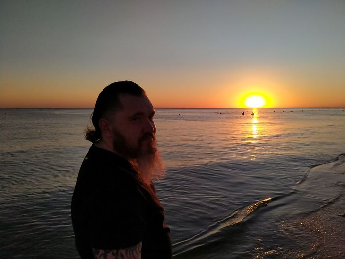 Man standing at beach against sky during sunset