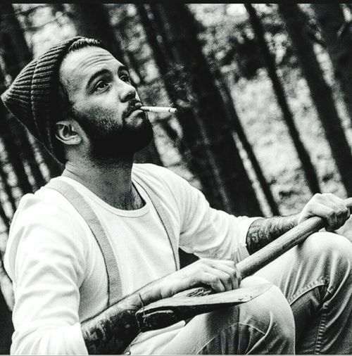 Lumberjack holding axe while smoking cigarette in forest