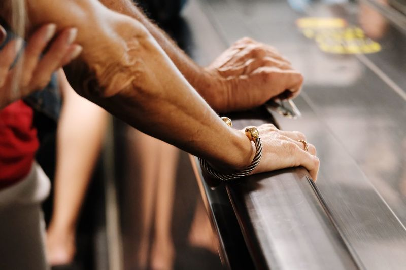 Cropped hands of people by railing of escalator
