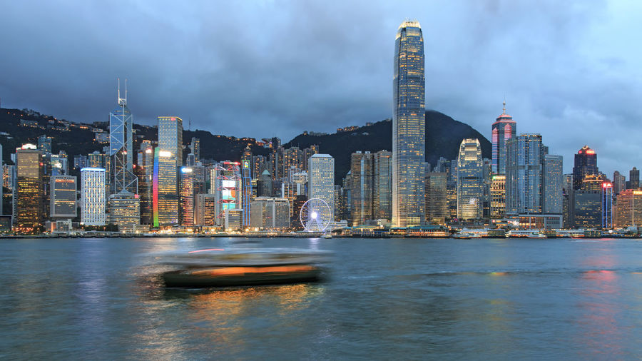 Blurred motion of boat sailing at victoria harbour against two international finance center