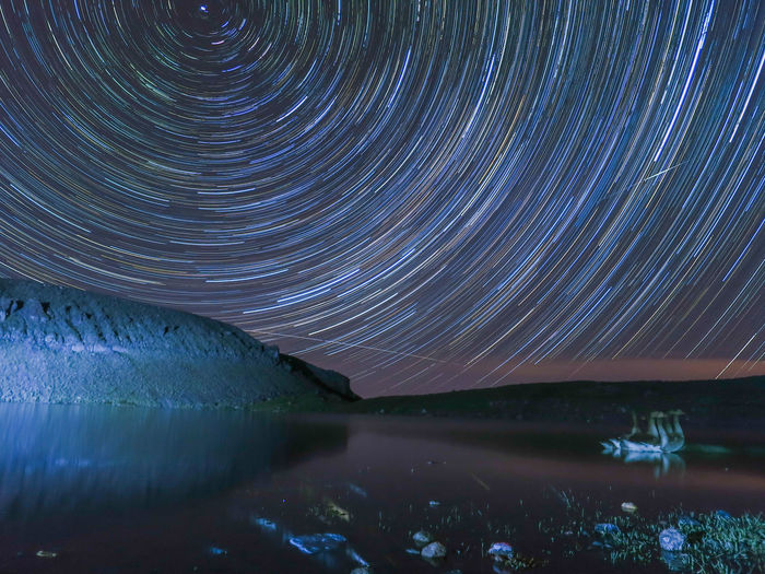 Scenic View Of Lake Against Illuminated Star Trails