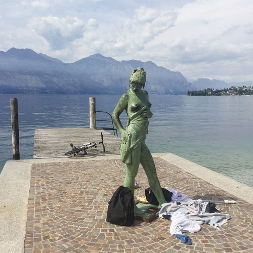 Statue by lake against sky