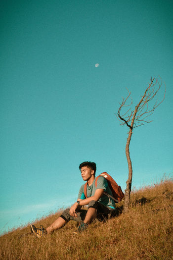 Young man sitting on field against clear blue sky