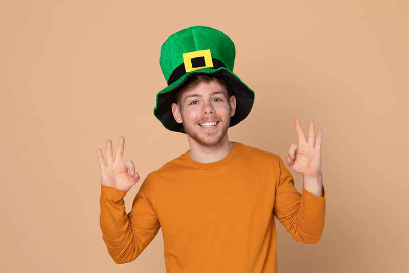 Smiling man wearing green hat standing against beige background