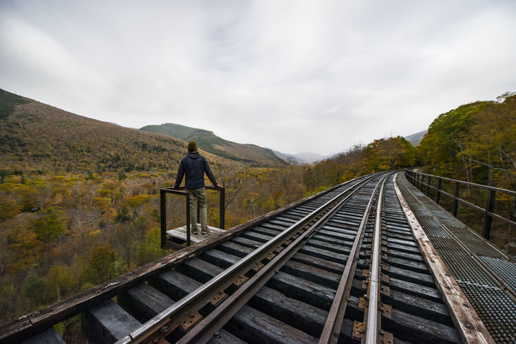 Rear view of person on railroad tracks against sky