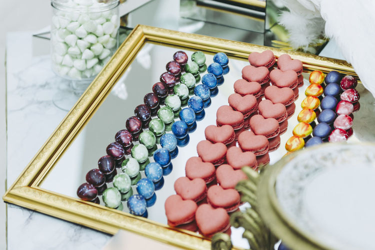High angle view of macaroons and candies on mirror