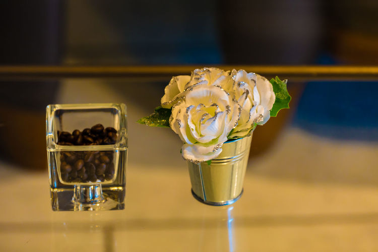 Close-Up Of Artificial Roses With Roasted Coffee Beans In Container On Glass Table