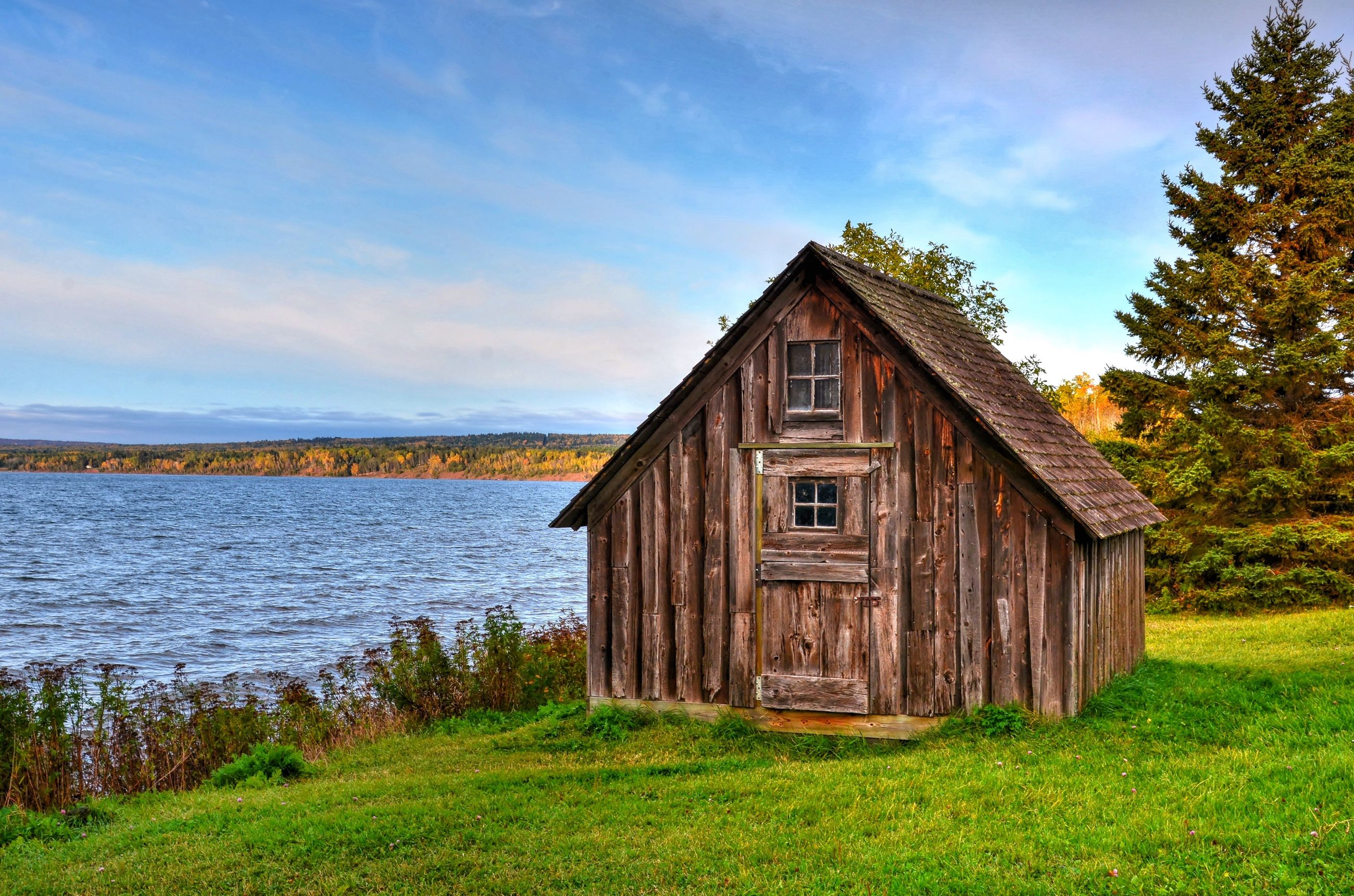 sky, built structure, architecture, house, building exterior, tranquility, rural scene, outdoors, cottage, tree, wood - material, no people, grass, day, green color, tranquil scene, nature, cabin, beauty in nature, water
