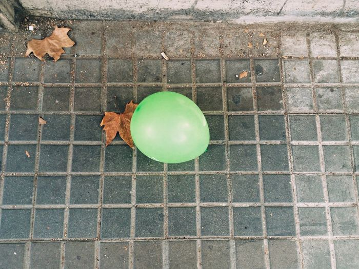 Green balloon on sidewalk