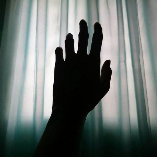 Cropped Image Of Silhouette Hand By Curtain