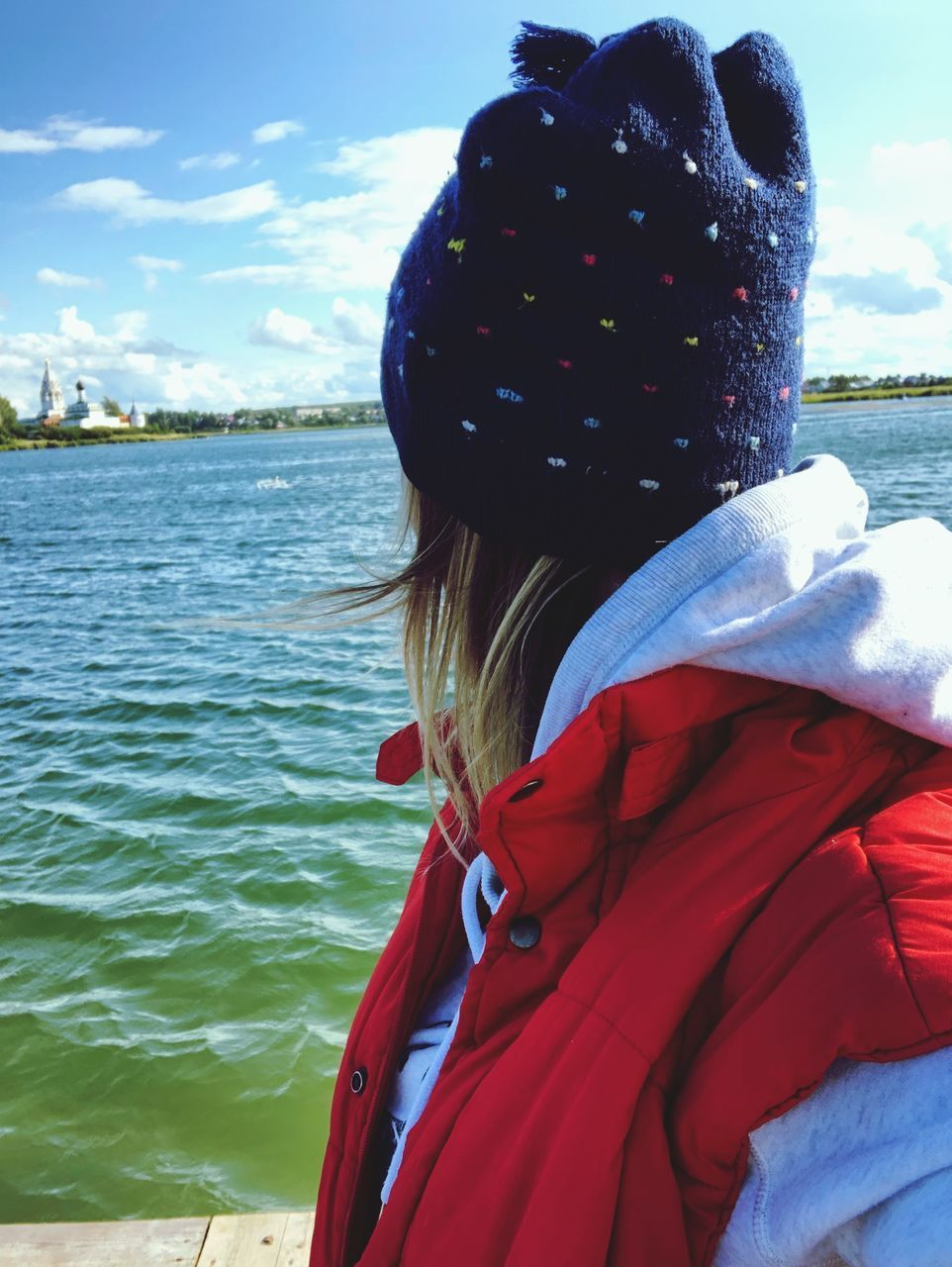 water, real people, rear view, one person, leisure activity, clothing, warm clothing, winter, child, lifestyles, women, day, portrait, hat, childhood, nature, waist up, red, scarf, outdoors, hood - clothing, looking at view