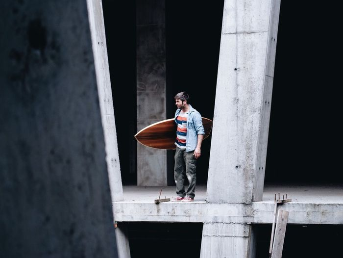 Full Length Of Man Carrying Surfboard While Standing In Incomplete Building
