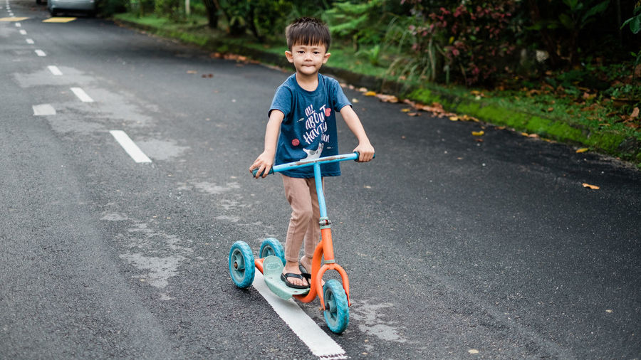 Boy riding push scooter on road in city