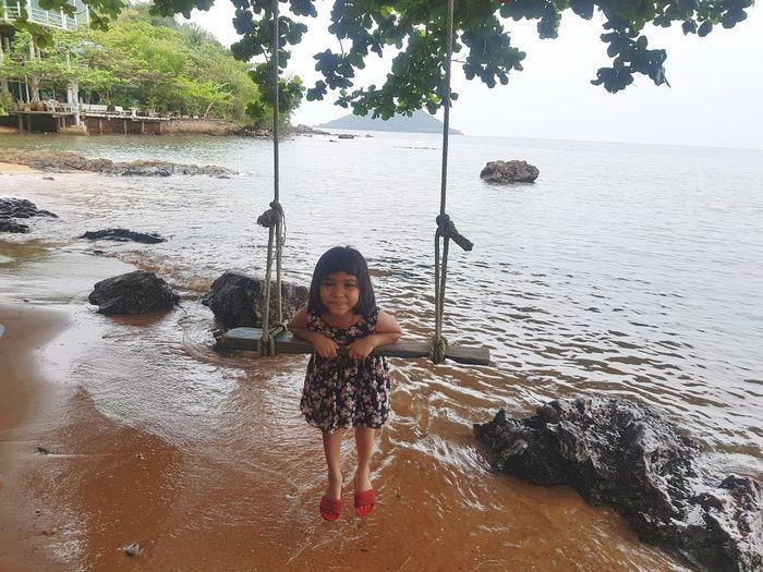 Portrait Of Smiling Girl Swinging At Beach