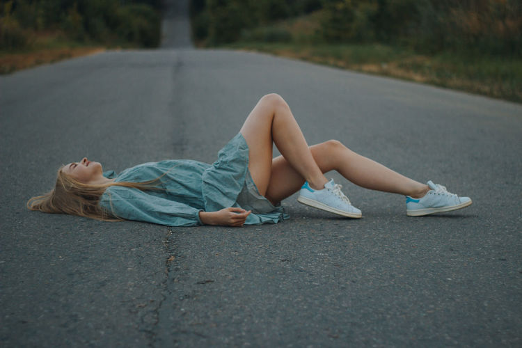 Woman lying on road in city