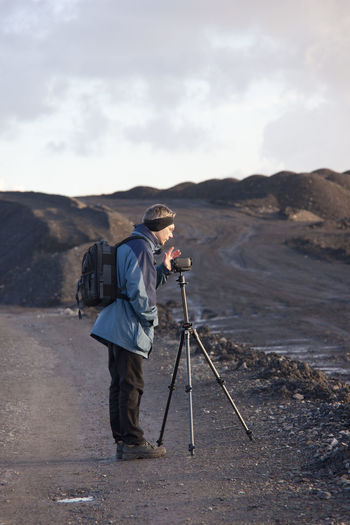 Side View Of Man Photographing While Standing Against Sky