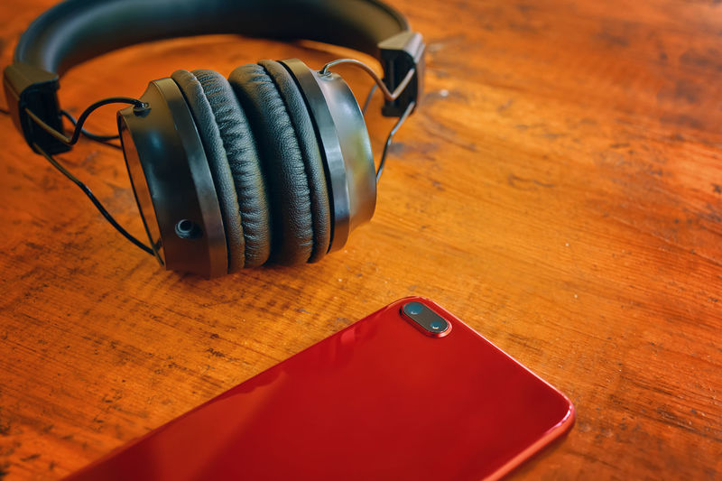 Close-up of mobile phone with headphones on table
