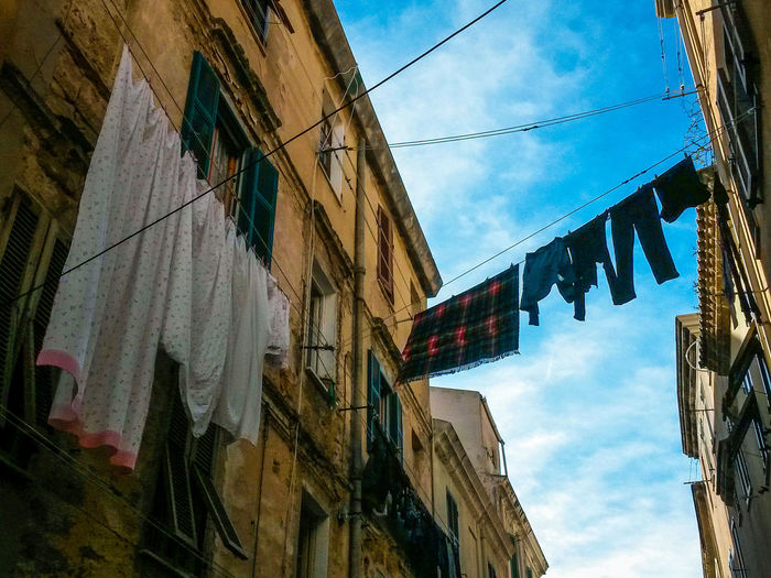 The Street Photographer - 2017 EyeEm Awards clothes and sheet drying in the open air Building Exterior Architecture Built Structure Low Angle View Outdoors Sky Day No People Hanging City Sheets Drying Drying Clothes Colour Your Horizn