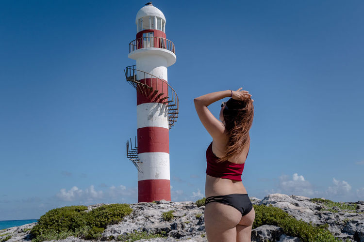 Woman standing by lighthouse against clear blue sky