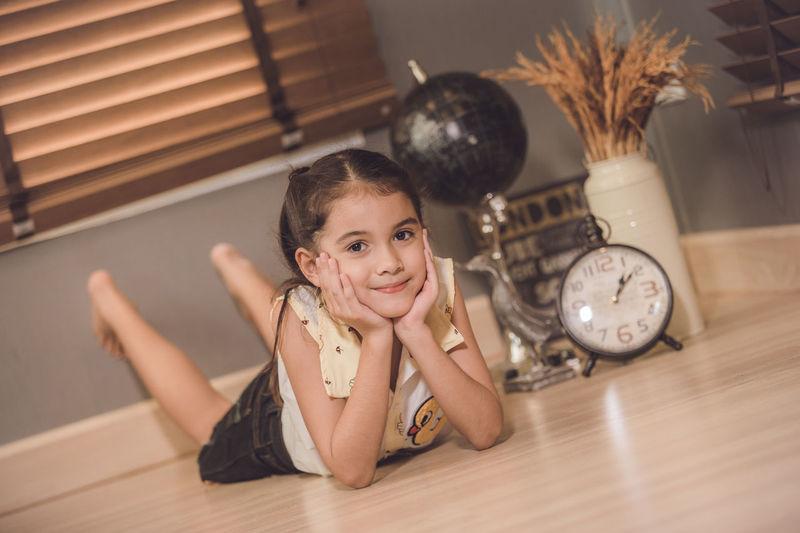 Full length portrait of cute smiling girl lying on floor at home