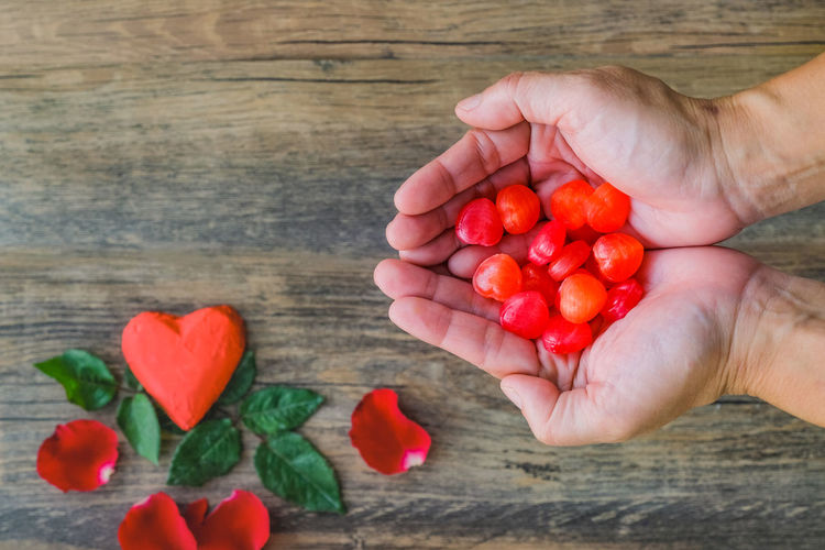 Cropped hand holding red berries on table
