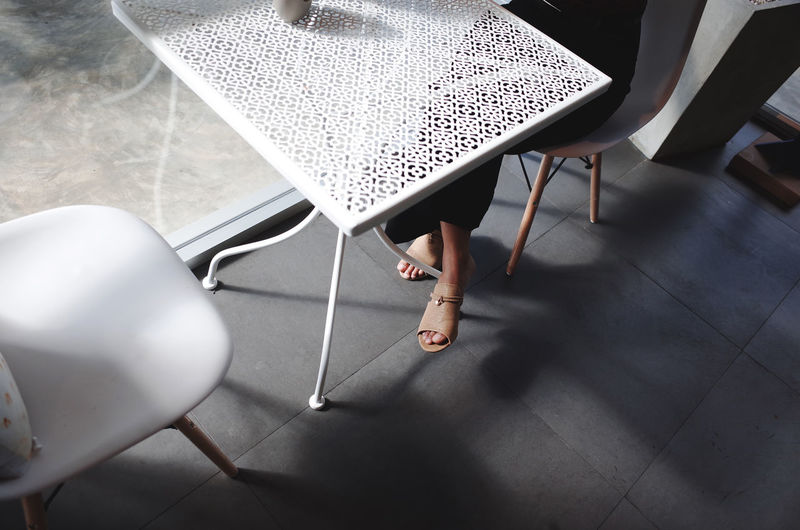Women sit on chair In office with light and shadow Low Section Seat Human Leg Human Body Part Chair High Angle View Body Part Real People Day People Adult Women Tile Flooring Lifestyles Sitting Shoe Tiled Floor Indoors  Human Foot