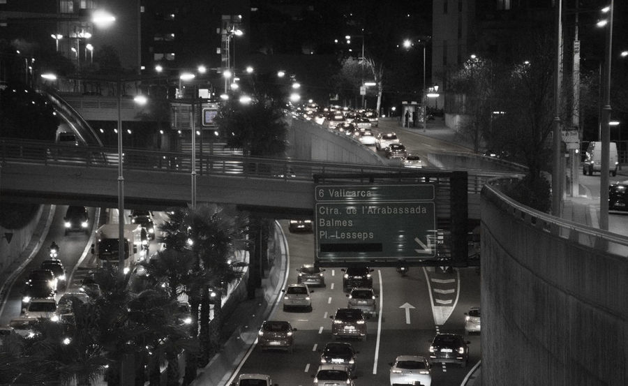 Dense traffic of cars on an exit highway of Barcelona city. Traffic Building Exterior City City Life Density High Angle View Highway Illuminated Land Vehicle Mode Of Transportation Motion Motor Vehicle Night No People Polution Real People
