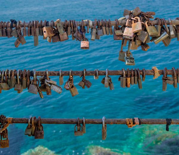 High angle view of padlocks on railing against sea