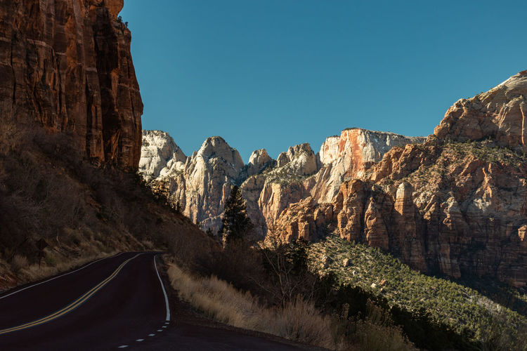 Road amidst rocky mountains against clear blue sky