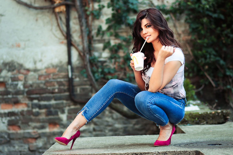 Jovana Adult Beautiful Woman Casual Clothing Day Drinking Focus On Foreground Food And Drink Full Length Hair Hairstyle Holding Jeans Leisure Activity Lifestyles Long Hair One Person Outdoors Portrait Real People Sitting Women Young Adult Young Women