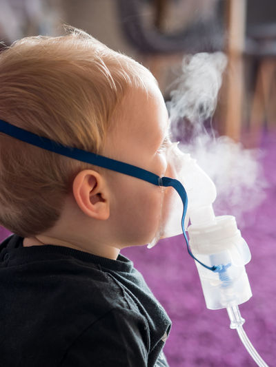 Cute blonde kid inhaling at home with oxygen mask Child Childhood Inhalation Kid Inhaler Medical Asthma Home Medicine Boy Health Allergy Asthmatic Care Respiratory Patient Treatment Young Sick Disease Illness Breathing Oxygen Mask Little Caucasian Face Therapy Airplane Flu Inhaling Medication Allergic Close-up Side View