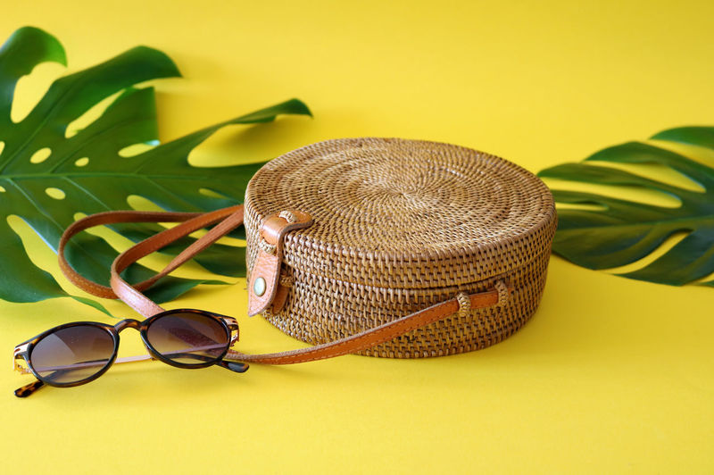 Round shaped Ata rattan boho bag with a leather strap and sunglasses laying on a Monstera leaf and yellow, sunny background. Bali Bohemian Ibiza Rattan Bag Beach Bag Boho Chic Circular Colored Background Fashion Glasses Leaf Leather Strap Leaves Monstera No People Personal Accessory Plant Round Shoulder Bag Still Life Sunglasses Trend Yellow