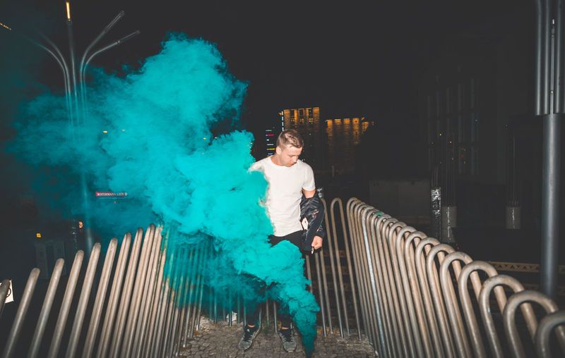 Black man in a leather jacket standing outside. Colorful portrait of European teenager with blue smoke bomb. Night time. Architecture Building Exterior Built Structure Casual Clothing Front View Full Length Illuminated Leisure Activity Lifestyles Night One Person Outdoors People Railing Real People Standing Young Adult