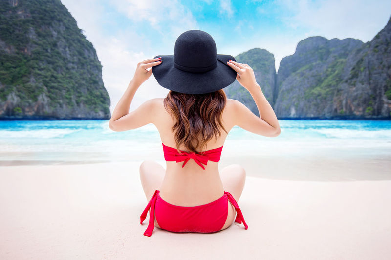Rear View Of Woman In Bikini While Sitting At Seashore Against Sky