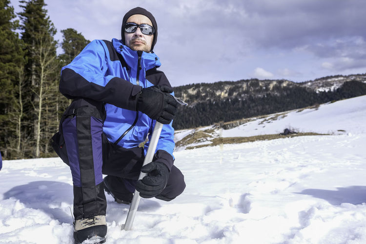 Photo of a mountain tourist in winter. Beauty In Nature Cloud - Sky Cold Temperature Day Field Full Length Fun Happiness Landscape Leisure Activity Lifestyles Looking At Camera Nature One Person Outdoors Portrait Real People Scenics Sky Smiling Snow Standing Tree Warm Clothing Winter