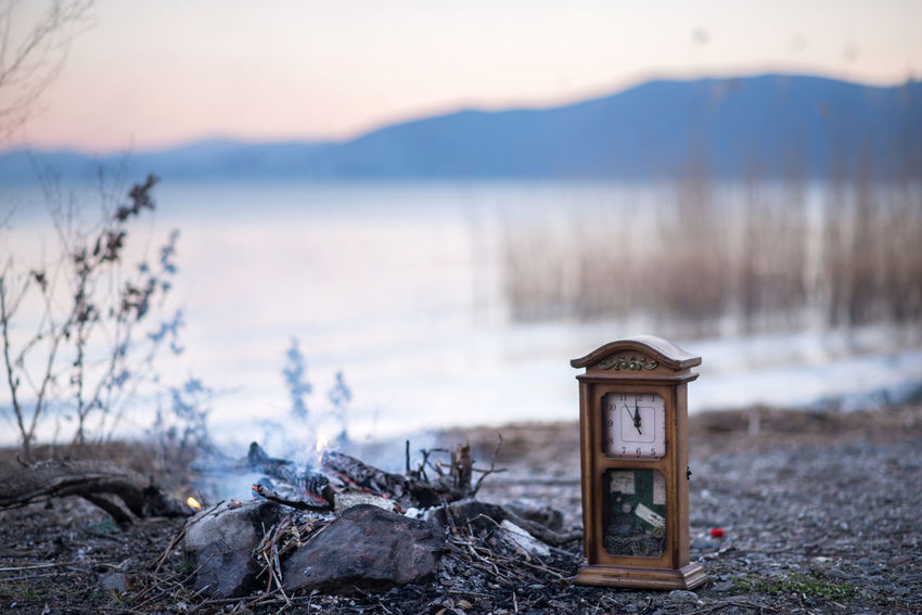 Beauty In Nature Clock Clockface Close-up Day Fire Focus On Foreground Lake Lake Prespa Macedonia Nature No People Outdoors Scenics Sky Smoke Sunset Time Concept Tranquility Wall Clock Water Wooden Post