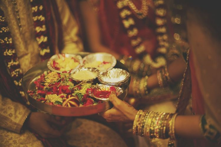 Midsection of woman holding religious offering by bride and groom during wedding