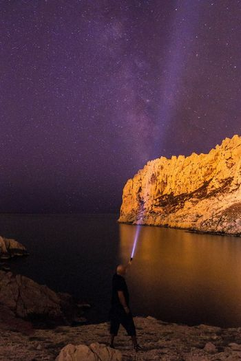 Rear view of man with flashlight standing by lake against milky way at night