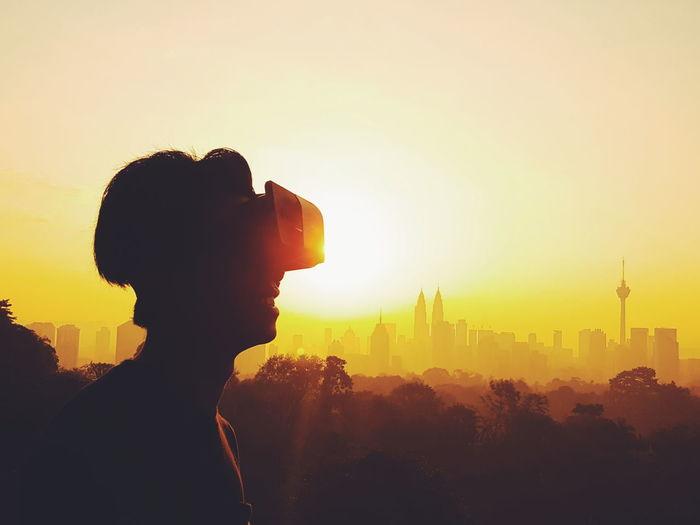 Silhouette man enjoying virtual reality simulator against orange sky