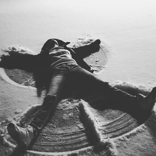 High Angle View Of Man Making Snow Angel