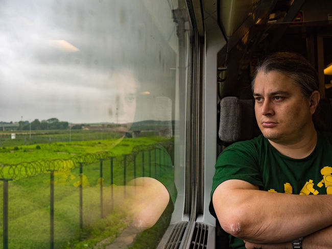 As the Eurostar approaches the Channel tunnel in France, a passenger gazes over the miles and miles of fences and barbed wire, protecting the border between France and Britain. This was Europe. Barbed Wire Border Border Control  Brexit Britain Calais  Casual Clothing Contemplation Copy Space Editorial  Euro Eurostar Feel The Journey Fence France Headshot Journey Looking Through Window On The Way Passenger Portrait Train Travel Window