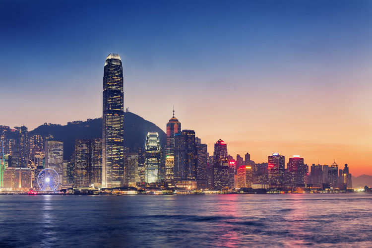 Victoria Harbor Against Illuminated Buildings In City At Sunset